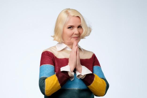 Starszy blond kobieta naciskając dłonie razem, mając żałobny wyraz twarzy