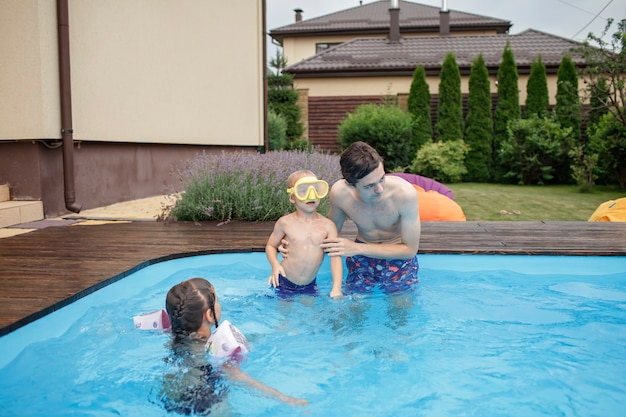 Starszy brat trenuje małe rodzeństwo do pływania w basenie na świeżym powietrzu w letnim zdrowym stylu życia