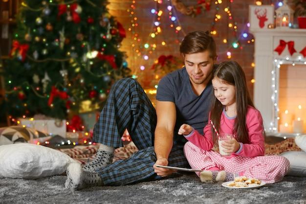 Starszy brat z młodszą siostrą używający tabletu i jedzący ciasteczka w świątecznym salonie