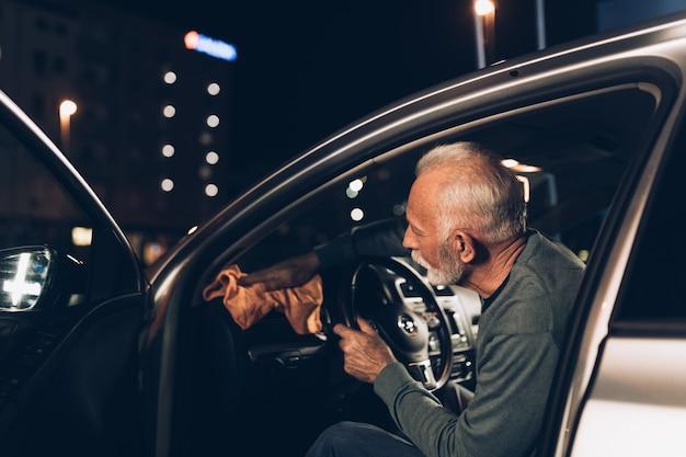 Starszy broda sprzątający wieczorem swój samochód odkurzaczem na myjni samochodowej