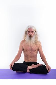 Starszy brodaty mężczyzna guru siedzi na macie do jogi ze skrzyżowanymi nogami