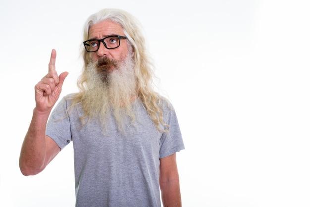 Starszy brodaty mężczyzna myśli i nosi okulary