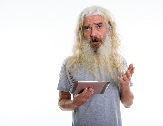 Starszy brodaty mężczyzna myśli trzymając cyfrowy tablet