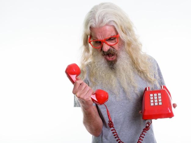 Starszy brodaty mężczyzna patrząc zły, krzycząc na telefon