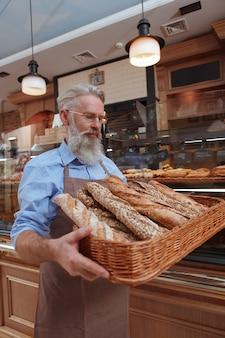 Starszy brodaty mężczyzna piekarz niosący świeżo upieczony chleb w koszu