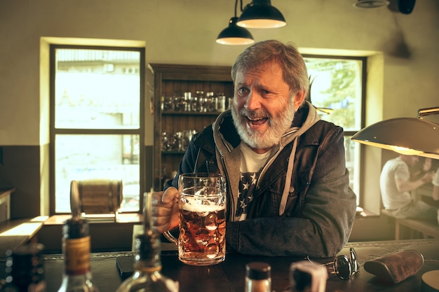 Starszy brodaty mężczyzna pije alkohol w pubie i ogląda program sportowy w telewizji. cieszę się moją ulubioną herbatą i piwem. mężczyzna z kuflem piwa siedzi przy stole. fan piłki nożnej lub sportu. koncepcja ludzkich emocji