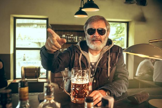 Starszy brodaty mężczyzna pije alkohol w pubie i ogląda program sportowy w telewizji. cieszę się moją ulubioną herbatą i piwem. mężczyzna z kuflem piwa siedzi przy stole.