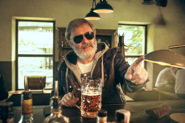 Starszy brodaty mężczyzna pije alkohol w pubie i ogląda program sportowy w telewizji. cieszę się moją ulubioną kawą i piwem. mężczyzna z kuflem piwa siedzi przy stole.