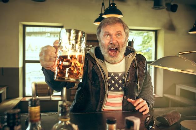 Starszy brodaty mężczyzna pije alkohol w pubie i ogląda program sportowy w telewizji.
