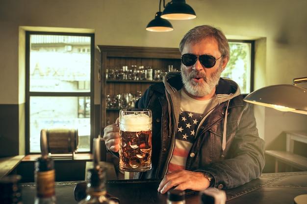 Starszy brodaty mężczyzna pije piwo w pubie