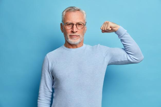 Starszy brodaty mężczyzna pokazuje mięśnie po treningu kulturystyki, nosi przezroczyste okulary i podstawowe pozy skoczka na tle niebieskiej ściany studia