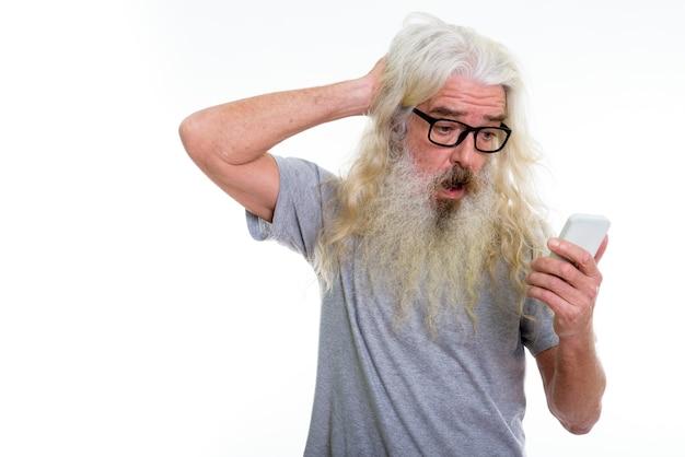 Starszy brodaty mężczyzna przy użyciu telefonu komórkowego
