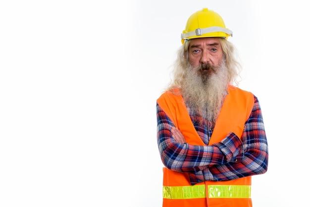 Starszy brodaty mężczyzna robotnik budowlany z rękami skrzyżowanymi