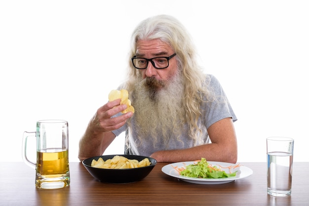 Starszy brodaty mężczyzna trzyma i patrząc na ziemniaka