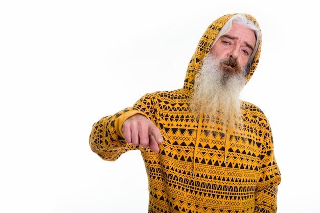 Starszy brodaty mężczyzna ubrany w bluzę z kapturem, wskazując na przód