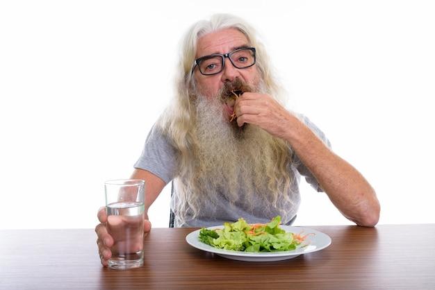 Starszy brodaty mężczyzna w okularach podczas jedzenia