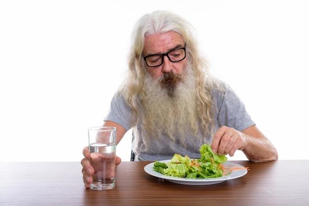 Starszy brodaty mężczyzna w okularach szklaną wodą