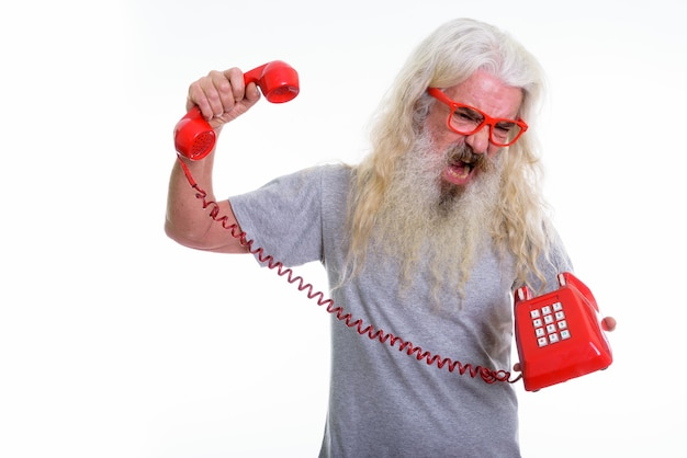Starszy brodaty mężczyzna zły i krzyczy, trzymając stary telefon