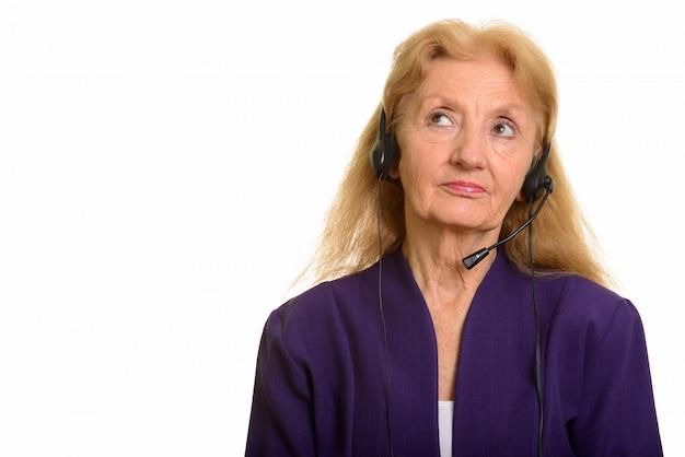 Starszy businesswoman noszenia słuchawek i myślenia pracy w centrum telefonicznym