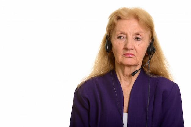 Starszy businesswoman noszenia słuchawek szuka zmęczonej pracy w call center