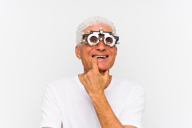 Starszy caucasian mężczyzna jest ubranym optometrist próby ramę relaksował myśleć o coś patrzeje odbitkową przestrzeń.