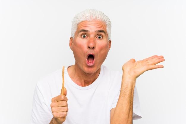 Starszy caucasian mężczyzna trzyma toothbrush odizolowywał imponującą mienie kopii przestrzeń na palmie.