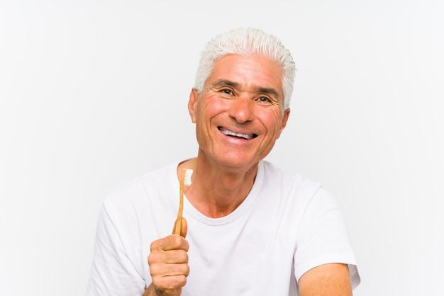 Starszy caucasian mężczyzna trzyma toothbrush odizolowywał ono uśmiecha się ufny z krzyżować rękami.