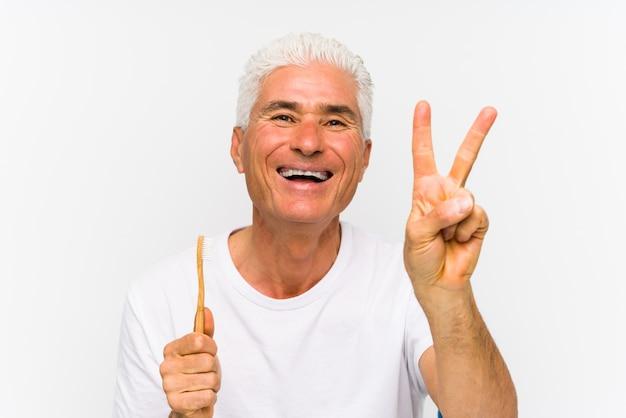 Starszy caucasian mężczyzna trzyma toothbrush odizolowywał pokazywać liczbę dwa z palcami.