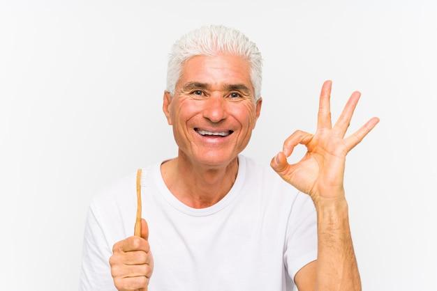 Starszy caucasian mężczyzna trzyma toothbrush odizolowywał rozochoconego i ufnego pokazuje ok gest.