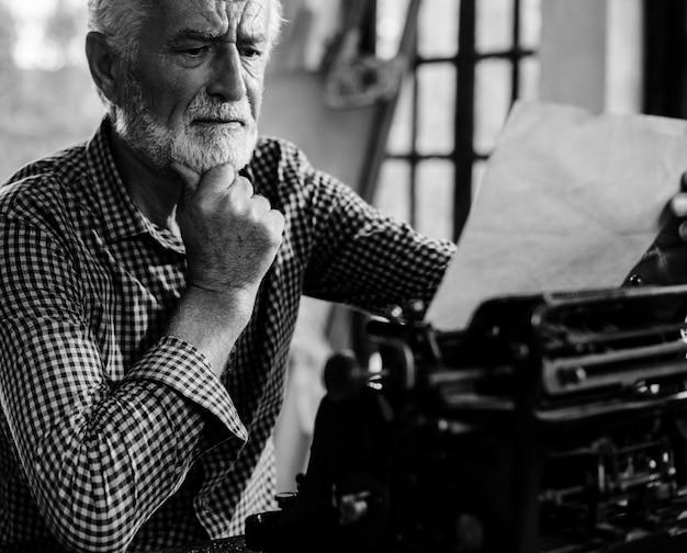 Starszy caucasian mężczyzna używa rocznika maszyna do pisania grayscale