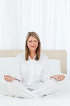 Starszy ćwiczy joga na jej łóżku