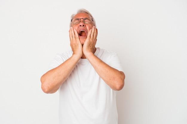 Starszy człowiek amerykański na białym tle płacz, niezadowolony z czegoś, agonii i koncepcji zamieszania.