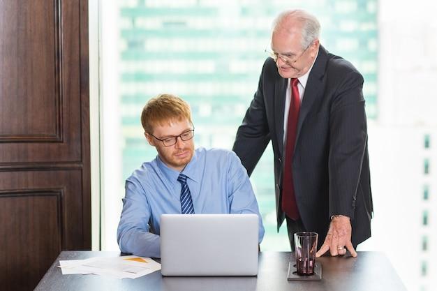 Starszy człowiek biznesu patrząc na pracę innego młodszego pracownika