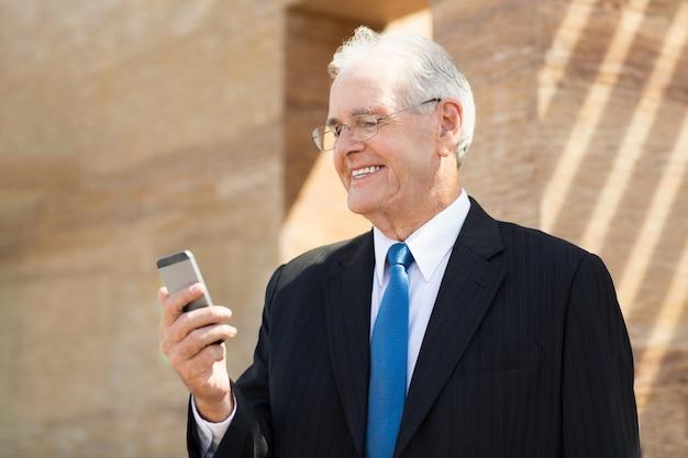 Starszy człowiek biznesu patrząc na telefon i uśmiechnięte