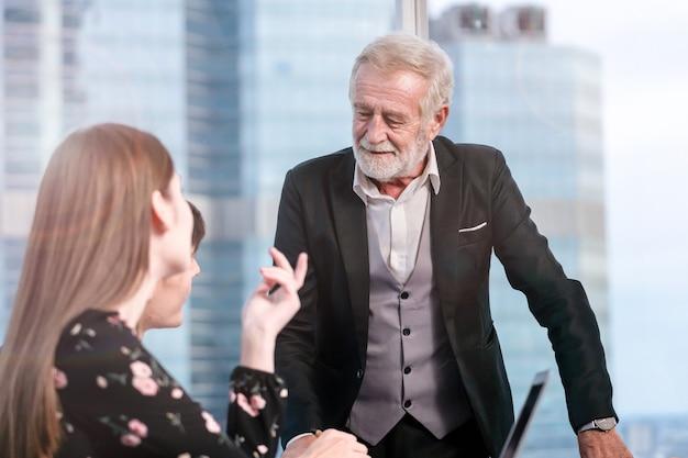 Starszy człowiek biznesu wyjaśniając sprawy biznesowe zespołowi w sali konferencyjnej.