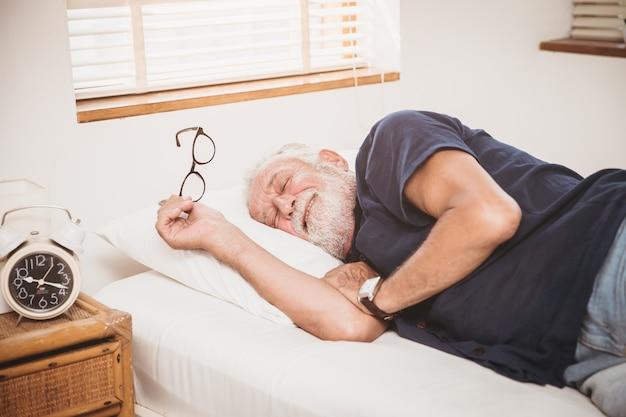 Starszy czuje się komfortowo leżąc na łóżku ciesz się spaniem lub drzemką obudź się rano dobrze zdrowy