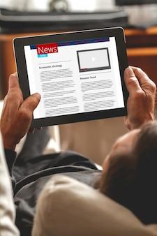 Starszy czytanie wiadomości na tablecie