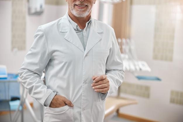 Starszy dentysta trzymający rękę w kieszeni i uśmiechający się w swoim gabinecie