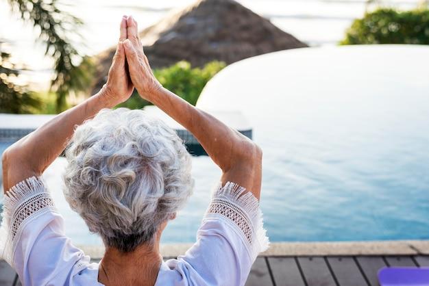 Starszy dorosły ćwiczyć joga przy basenem