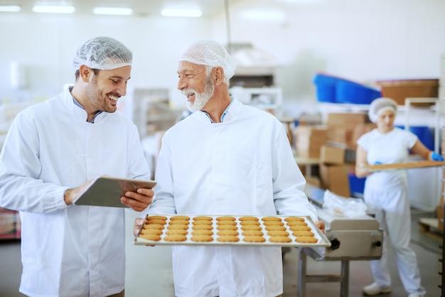 Starszy dorosły pracownik trzyma tacę ze świeżymi ciasteczkami, podczas gdy przełożony ocenia jakość i trzyma tablet. oboje ubrani są w sterylne białe mundury i mają siatki na włosy. wnętrze zakładu spożywczego.
