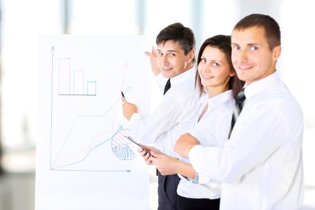 Starszy dyrektor biznesowy przedstawia prezentację swoim współpracownikom podczas spotkania lub wewnętrznego szkolenia biznesowego