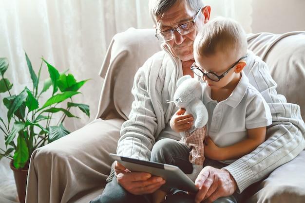 Starszy dziadek i jego mały wnuk używają tabletu, uśmiechając się i bawiąc się lub oglądając śmieszne wideo w internecie, siedząc na krześle