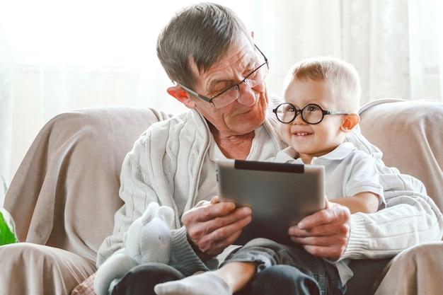 Starszy dziadek i jego mały wnuk używają tabletu