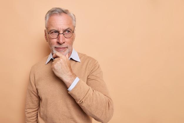 Starszy dziadek stoi w zamyślonej pozie, trzymając podbródek patrząc w dal