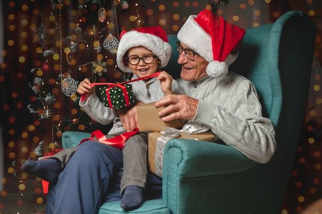 Starszy dziadek z wnukiem w czapkach mikołaja daje i otwiera prezenty świąteczne