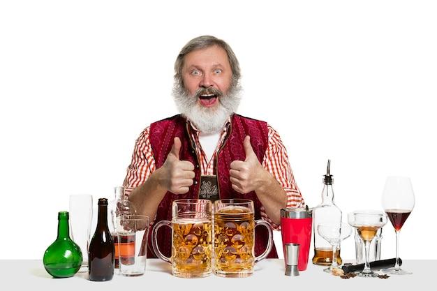Starszy ekspert męski barman z piwem na na białym tle na białej ścianie. międzynarodowy dzień barmana, bar, alkohol, restauracja, piwo, impreza, pub, koncepcja obchodów dnia świętego patryka