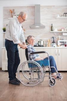 Starszy emeryt pomagający żonie z niepełnosprawnością ruchową. niepełnosprawnych starszy kobieta siedzi na wózku inwalidzkim w kuchni patrząc przez okno. mieszkanie z osobą niepełnosprawną. mąż pomaga żonie z d