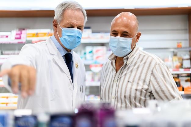 Starszy farmaceuta zajmujący się klientem, oboje w maskach z powodu koronawirusa