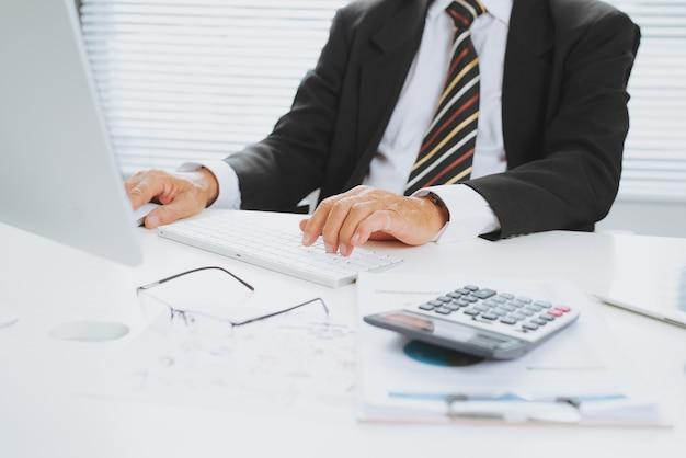 Starszy finansowy biznesmen azjatyckich siedzi przy swoim stanowisku pracy przed komputerem.