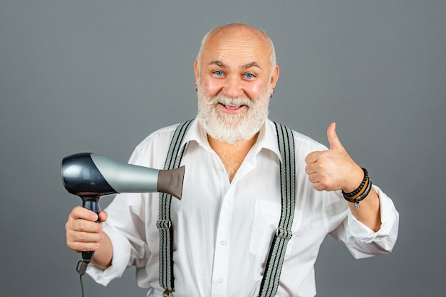 Starszy fryzjer lub fryzjer z szczęśliwą emocjonalną twarzą w studio na szarym tle. mężczyzna z suszarką z kciukiem do góry.